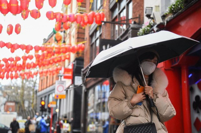 A woman wearing a face mask in China Town, Leicester Square