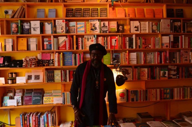 Dele Adejobi in front of a bookcase