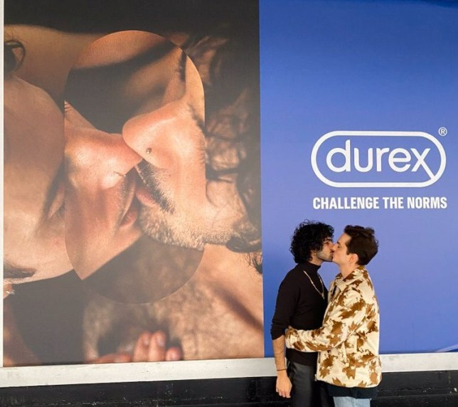 TWO MEN KISSING IN FRONT OF A POSTER OF THEM KISSING