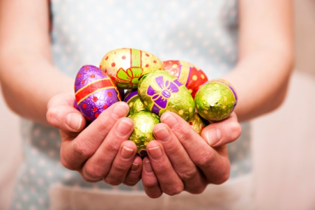 Woman with her hands full of brightly colored chocolate Easter eggs.