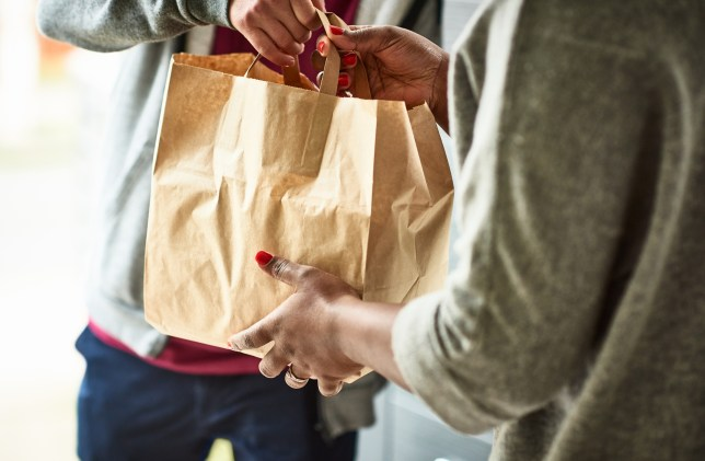 woman holding a paper bag with groceries