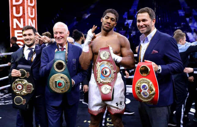 Anthony Joshua poses for a photo with the IBF, WBA, WBO & IBO World Heavyweight Title belts with Eddie Hearn and Barry Hearn after the IBF, WBA, WBO & IBO World Heavyweight Title Fight between Andy Ruiz Jr and Anthony Joshua during the Matchroom Boxing 'Clash on the Dunes' show at the Diriyah Season on December 07, 2019 in Diriyah, Saudi Arabia