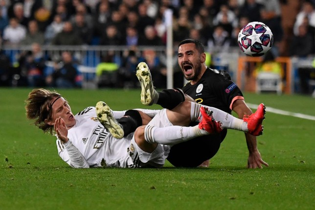 TOPSHOT - Real Madrid's Croatian midfielder Luka Modric (L) falls with Manchester City's German midfielder Ilkay Gundogan during the UEFA Champions League round of 16 first-leg football match between Real Madrid CF and Manchester City at the Santiago Bernabeu stadium in Madrid on February 26, 2020. (Photo by PIERRE-PHILIPPE MARCOU / AFP) (Photo by PIERRE-PHILIPPE MARCOU/AFP via Getty Images)