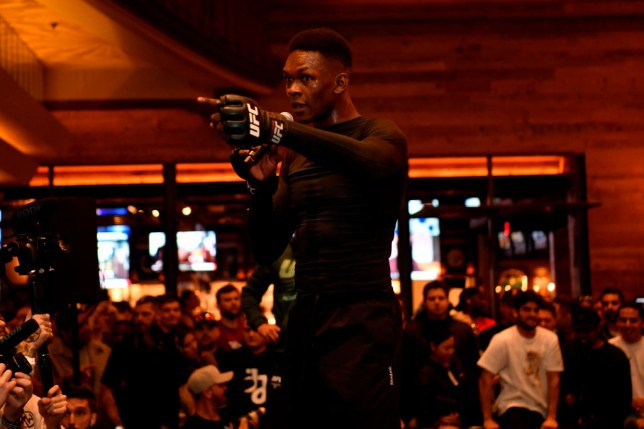 Israel Adesanya points at a fan during an open workout for his UFC fight
