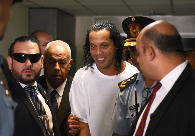 TOPSHOT - Brazilian retired football player Ronaldinho (C) arrives at Asuncion's Justice Palace to testify about his irregular entry to the country, in Asuncion, on March 6, 2020. - Former Brazilian football star Ronaldinho and his brother have been detained in Paraguay after allegedly using fake passports to enter the South American country, authorities said Wednesday. (Photo by Norberto DUARTE / AFP) (Photo by NORBERTO DUARTE/AFP via Getty Images)