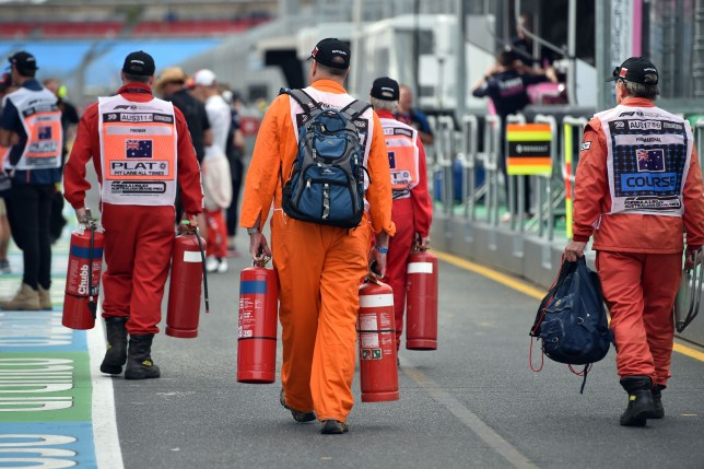 Pit marshals walk towards the garages before the first practice session for the Formula One Australian Grand Prix in Melbourne.