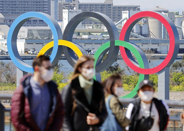 people in masks walk past olympic rings