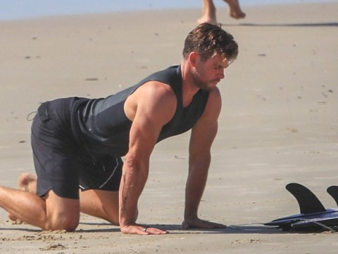 Chris Hemsworth perfects his downward-facing dog during beach yoga with brother Liam