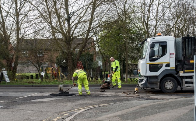 Reading, UK - March 8 2019: Workmen fix holes in the road by laying new tarmac.; Shutterstock ID 1333102682; Purchase Order: -