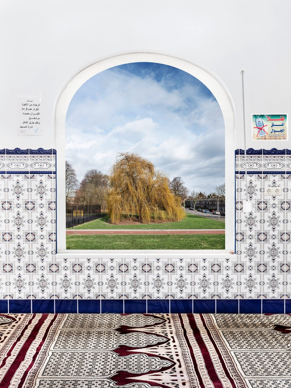 NEW DUTCH VIEWS Photographer Marwan Bassiouni (b. 1985, Switzerland) visited over seventy of the four hundred or so mosques in the Netherlands between January 2018 and February 2019. He made his choice of which spaces to photograph based on the views that their windows had to offer on the local surroundings. His composite images show real interiors combined with the actual view from the mosque. In his series New Dutch Views, Bassiouni shows the diversity of Islam in apparent contrast with the equally diverse yet instantly recognizable Dutch landscape. Bassiouni?s sharply focused and detailed photographs question how Islam is represented in the West, and show a society in which several cultures exist alongside and with each other. New Dutch Views is a symbolic portrait of Bassiouni?s double cultural background, and it highlights the fact that a new Western Islamic identity is emerging. In his first solo exhibition at the Photography Museum of the Hague seventeen large-scale photographs are accompanied by the photographer?s own biographical reflections. The New Dutch Views book counts all thirty photographs and short texts of the series. The latter are intimately placed at the back of each photograph requiring one to delicately manipulate the pages in order to access the content.