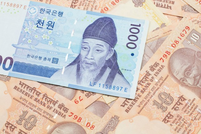 A blue South Korean one thousand won bank note close up in macro on a background of Indian ten rupee bank notes