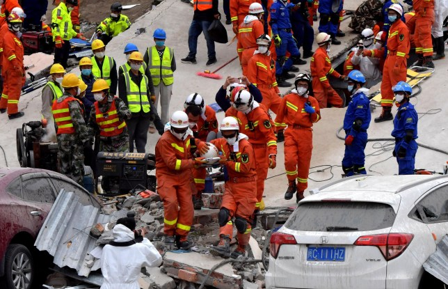 QUANZHOU, CHINA - MARCH 08: Rescuers carry an injured person on the rubble of a collapsed hotel on March 8, 2020 in Quanzhou, Fujian Province of China. A hotel building collapsed in Quanzhou city of east China's Fujian Province on Saturday evening, killing at least four people. 49 have been rescued as of 8:20 a.m. Sunday. (Photo by Zhang Bin/China News Service via Getty Images)