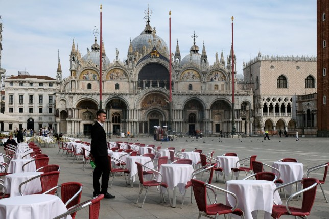 A waiter stands by empty tables outside a restaurant at St Mark's Square after the Italian government imposed a virtual lockdown on the north of Italy including Venice to try to contain a coronavirus outbreak, in Venice, Italy, March 9, 2020. REUTERS/Manuel Silvestri