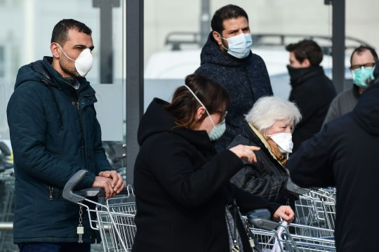 Residents wearing respiratory mask wait to be given access to shop in a supermarket in small groups of forty people on February 23, 2020 in the small Italian town of Casalpusterlengo, under the shadow of a new coronavirus outbreak, as Italy took drastic containment steps as worldwide fears over the epidemic spiralled. (Photo by Miguel MEDINA / AFP) (Photo by MIGUEL MEDINA/AFP via Getty Images)