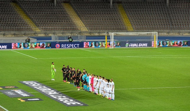 pro football players line up to play in front of an empty staduim