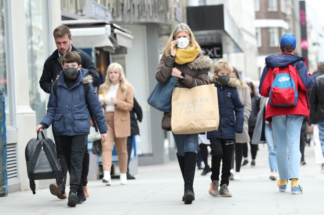 A woman wearing a protective face mask walking down Oxford Street in London, as the Government's top scientist warned that up to 10,000 people in the UK are already infected. PA Photo. Picture date: Friday March 13, 2020. See PA story HEALTH Coronavirus. Photo credit should read: Yui Mok/PA Wire