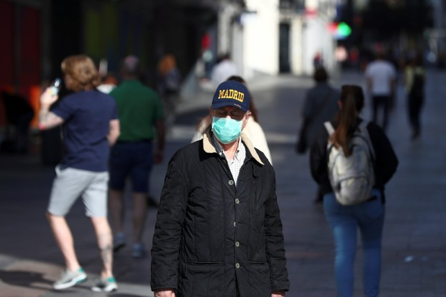A man, wearing a protective mask, walks through an empty street due to the coronavirus outbreak in Madrid