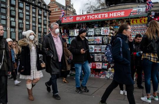 LONDRA, INGHILTERRA - 14 MARZO: Un uomo e una donna che indossano le maschere per il viso passano davanti a una bancarella di souvenir sul ponte di Westminster mentre lo scoppio del coronavirus si è intensificato il 14 marzo 2020 a Londra, Inghilterra. Molti londinesi e turisti stanno continuando le loro attività quotidiane mentre le riunioni di massa potrebbero essere bandite nel Regno Unito già dal prossimo fine settimana quando lo scoppio del coronavirus si intensificasse. Molte nazioni in Europa hanno già introdotto severi divieti di viaggio e limiti alla vita quotidiana dei loro cittadini mentre gli Stati Uniti hanno sospeso i viaggi in arrivo dai paesi europei. (Foto di Chris J Ratcliffe / Getty Images)