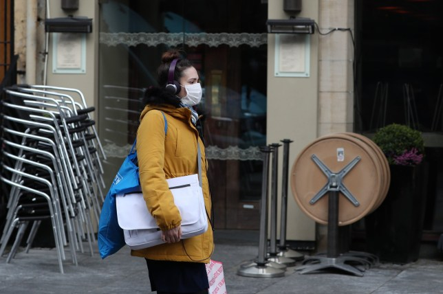 A woman wearing a mask walks past a closed restaurant in Edinburgh