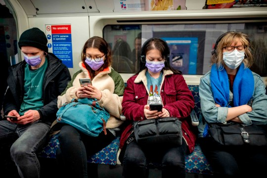 Commuters wear masks as a precaution whilst travelling on a London Underground metro train in the morning in central London on March 18, 2020 as people take precautions amid the coronavirus outbreak. - The British government will on Wednesday unveil a raft of emergency powers to deal with the coronavirus epidemic, including proposals allowing police to detain potentially infected people to be tested. (Photo by Tolga AKMEN / AFP) (Photo by TOLGA AKMEN/AFP via Getty Images)