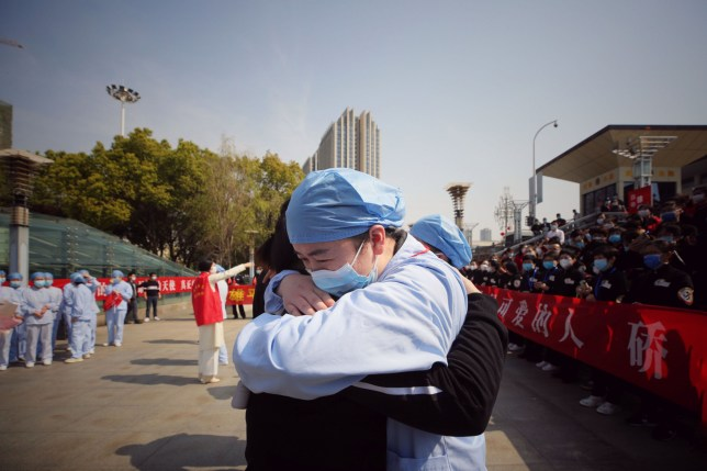 TOPSHOT - A medical worker (R) embraces a member of a medical assistance team from Jiangsu province at a ceremony marking their departure after helping with the COVID-19 coronavirus recovery effort, in Wuhan, in China's central Hubei province on March 19, 2020. - Medical teams from across China began leaving Wuhan this week after the number of new coronavirus infections dropped. China on March 19 reported no new domestic cases of the coronavirus for the first time since it started recording them in January, but recorded a spike in infections from abroad. (Photo by STR / AFP) / China OUT (Photo by STR/AFP via Getty Images)