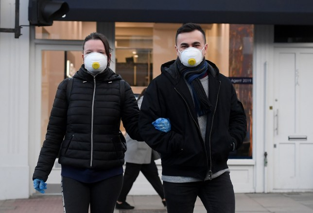 A couple wearing protective masks walk across a street in Clapham