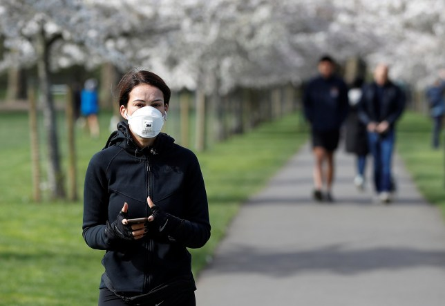 A woman wearing a protective face mask walks by blossom trees in Battersea Park as the spread of the coronavirus disease (COVID-19) continues. London, Britain March 21, 2020 REUTERS/Peter Nicholls