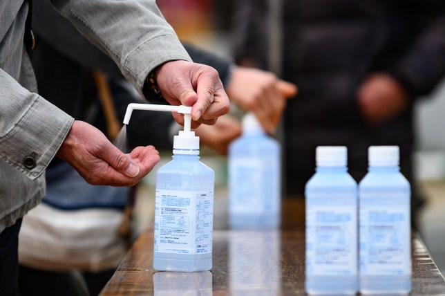 People clean their hands with hand sanitiser before entering the area to view the Tokyo 2020 Olympic flame on display at Ofunato, Iwate prefecture on March 23, 2020. - The flame arrived on March 20 in Miyagi prefecture north of Tokyo, following the traditional lighting ceremony in Greece which took place without spectators due to the ongoing worldwide COVID-19 coronavirus outbreak. (Photo by Philip FONG / AFP) (Photo by PHILIP FONG/AFP via Getty Images)