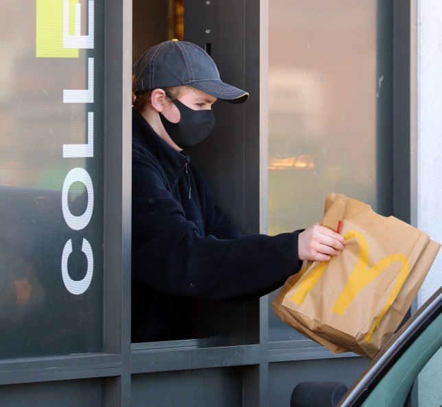 An employee wears a mask to serve customers at a McDonald's drive-thru near Dover in Kent as it was announced that all of their restaurant locations in the UK and Ireland will close by 7pm on Monday to protect the safety of their employees and customers from coronavirus.PA Photo. Picture date: Monday March 23, 2020. See PA story HEALTH Coronavirus. Photo credit should read: Gareth Fuller/PA Wire