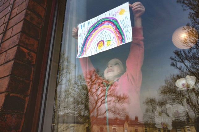 a young girl pins a rainbow poster to her window