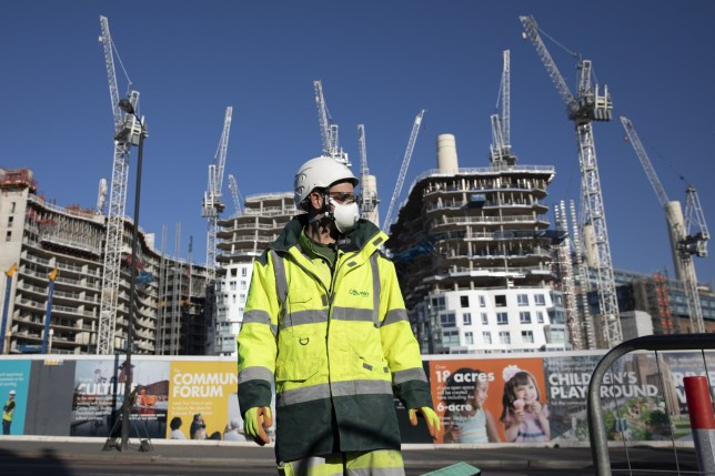 LONDON, ENGLAND - MARCH 25: Construction workers wear masks and maintain social distancing as they continue working near Battersea Power Station on March 25, 2020 in London, England. British Prime Minister, Boris Johnson, announced strict lockdown measures urging people to stay at home and only leave the house for basic food shopping, exercise once a day and essential travel to and from work. The Coronavirus (COVID-19) pandemic has spread to at least 182 countries, claiming over 18,000 lives and infecting hundreds of thousands more. (Photo by Dan Kitwood/Getty Images)