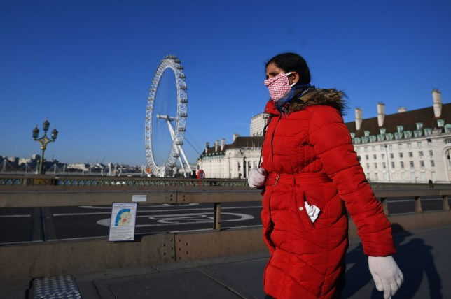 A woman wearing a facemask walking on a quiet Westminster Bridge,