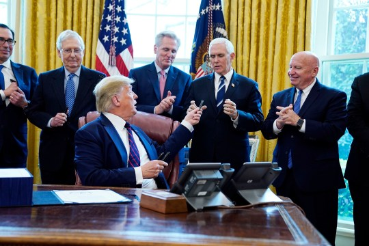 President Donald Trump hands a signing pen to Vice President Mike Pence after signing the coronavirus stimulus relief package, at the White House, Friday, March 27, 2020, in Washington. (AP Photo/Evan Vucci)