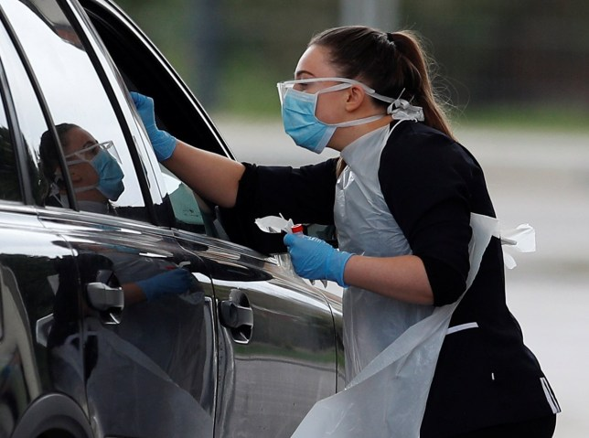 Medical staff at an NHS drive through coronavirus disease (COVID-19) testing facility in the car park of Chessington World of Adventures, as the spread of the coronavirus disease (COVID-19) continues, Chessington, Britain, March 30, 2020. REUTERS/Peter Nicholls