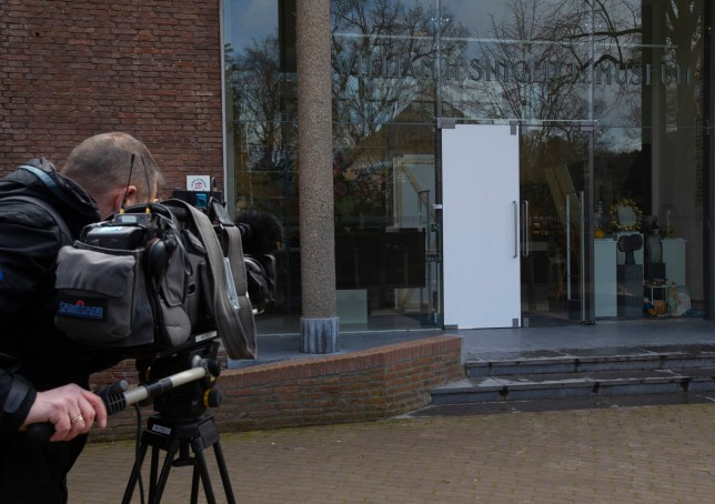 A cameraman films the glass door which was smashed during a break-in at the Singer Museum in Laren, Netherlands, Monday March 30, 2020. Police are investigating a break-in at a Dutch art museum that is currently closed because of restrictions aimed at slowing the spread of the coronavirus, the museum and police said Monday. (AP Photo/Peter Dejong)
