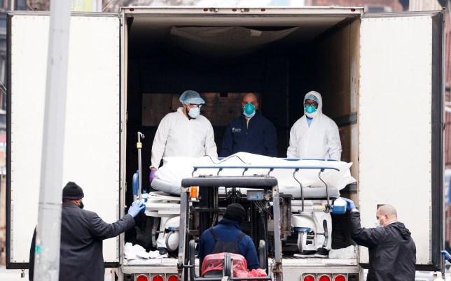 epa08333050 Medical professionals and hospital employees transfer a body on a hospital gurney into temporary storage in a mobile morgue, being used due to lack of space at the hospital, outside of the Brooklyn Hospital Center in Brooklyn, New York, USA, on 30 March 2020. New York City is still the epicenter of the coronavirus outbreak in the United States and as of Monday there were reportedly 1,218 people who have died as a result of complications from COVID-19. EPA/JUSTIN LANE