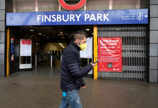 A man wearing a face mask as a precaution against COVID-19, Xwalks after Finsbury Park tube station in north London on March 31, 2020, as life in Britain continues during the national lockdown to combat the new coronavirus pandemic. - The new coronavirus pandemic has so far caused nearly 38,000 deaths worldwide in a health crisis that is rapidly reorganizing political power, hammering the world economy and the daily lives of some 3.6 billion people. (Photo by Isabel INFANTES / AFP) (Photo by ISABEL INFANTES / AFP via Getty Images)