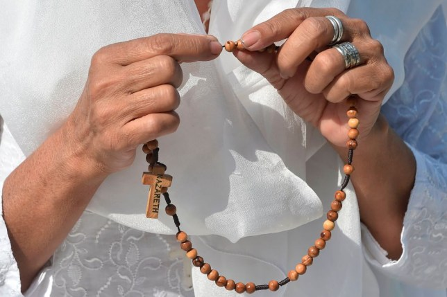 A woman devotee holds a rosary while she prays as she attends a Palm Sunday service