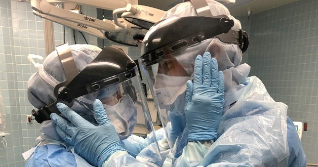 Nurse couple embracing each other while in protective equipment