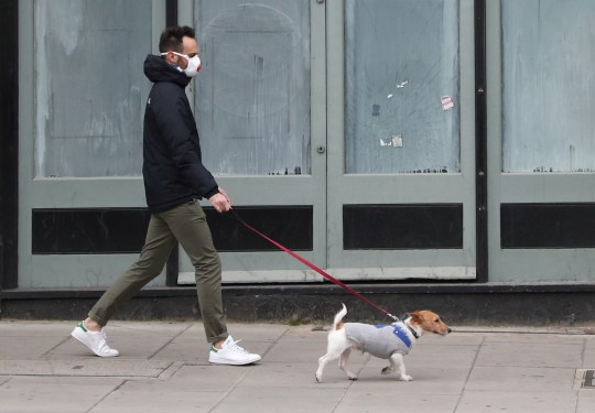A man is seen wearing a protective face mask as he walks a dog on Clapham High Street as the spread of the coronavirus disease (COVID-19) continues, London, Britain, March 28, 2020. REUTERS/Hannah McKay