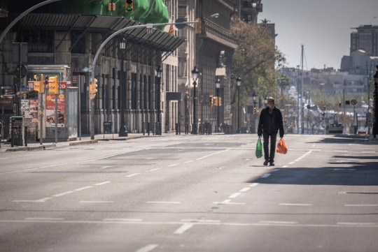Mandatory credit: Photo by Paco Freire / SOPA Images / REX (10603166e) A man walks on the deserted road to V? A Laietana carrying shopping bags during the contagion of Covid-19. Barcelona is facing its twenty-first day of home confinement. After the announcement of the President of the Spanish government, Pedro S? Nchez, to extend the confinement of the house, Spanish citizens will be confined until April 25. Home detention in Barcelona, Spain - April 04, 2020