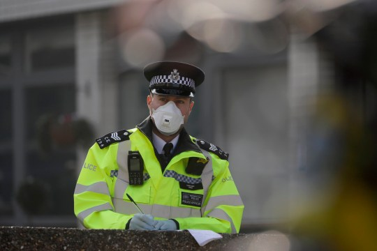 A British police officer wears a 3M face mask, with few police officers in Britain seen wearing face masks since the outbreak of the coronavirus, outside St Thomas' Hospital, in London, where Prime Minister Boris Johnson remains in intensive care as his coronavirus symptoms persist, Thursday, April 9, 2020. British Prime Minister Boris Johnson remains in intensive care with the coronavirus but is improving and sitting up in bed, a senior government minister said Wednesday, as the U.K. recorded its biggest spike in COVID-19 deaths to date. The new coronavirus causes mild or moderate symptoms for most people, but for some, especially older adults and people with existing health problems, it can cause more severe illness or death. (AP Photo/Kirsty Wigglesworth)