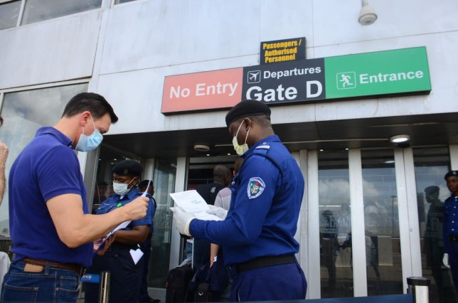 A security official screening a man during an evacuation of EU (European Union) citizens members includes Germany, France, Austria, Italy, Spain, Sweden, Greece, Ireland, among others, as the Federal Government had restricted flights from some of these countries identified as high-risk C9OVID-19 places before finally shutting all international airports in the country, in Lagos, Nigeria April 9, 2020. Following the Nigerian government approval the states lockdown was imposed, to contain the spread of COVID-19 coronavirus, by Nigerian President Mohammadu Buhari to cushion the effect of a two-week lockdown.