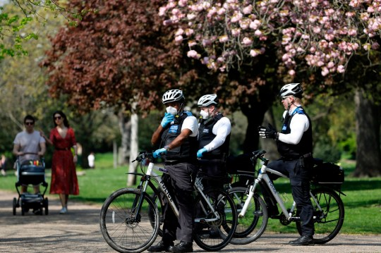 Officers of the Metropolitan Police patro in Victoria Park, east London on April 11, 2020 as warm weather tests the nationwide lockdown due to the novel coronavirus COVID-19 and the long Easter weekend begins. - The disease has struck at the heart of the British government, infected more than 60,000 people nationwide and killed over 8,000, with a daily death toll in England of 866 reported on April 10. (Photo by Tolga AKMEN / AFP) (Photo by TOLGA AKMEN/AFP via Getty Images)