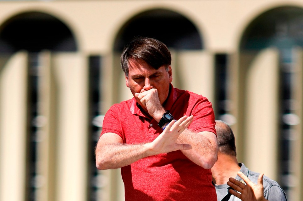 Brazilian President Jair Bolsonaro coughs as he speaks after joining his supporters who were taking part in a motorcade to protest against quarantine and social distancing measures to combat the new coronavirus outbreak in Brasilia on April 19, 2020. (Photo by Sergio LIMA / AFP) (Photo by SERGIO LIMA/AFP via Getty Images)