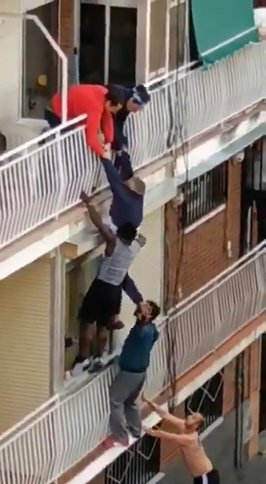 Pic Shows: Man hanging from a balcony during lockdown; This is the dramatic moment neighbours climb up a building to rescue a 70-year-old man hanging from a balcony and they manage to safely drop him onto a mattress below.