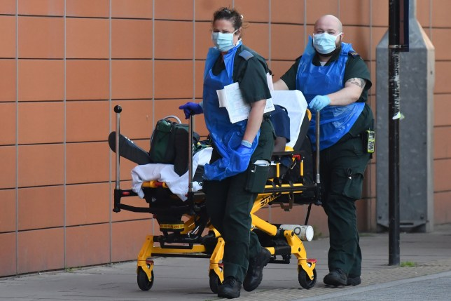 Paramedics wheel a patient into The Royal London Hospital in east London on April 21, 2020, during the novel coronavirus COVID-19 pandemic. (Photo by Handout / AFP) (Photo by HANDOUT/AFP via Getty Images)