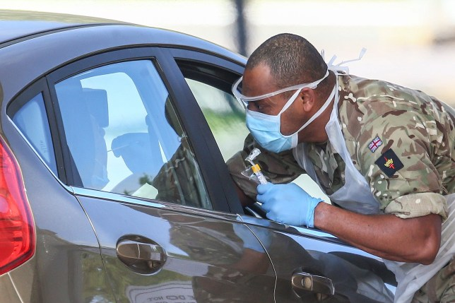CHESSINGTON, ENGLAND - APRIL 25: A military person takes a swab at a drive-in COVID-19 testing centre at Chessington World of Adventures Resort theme park on April 24, 2020 in Chessington, United Kingdom. The British government has extended the lockdown restrictions first introduced on March 23 that are meant to slow the spread of COVID-19. (Photo by Hollie Adams/Getty Images)
