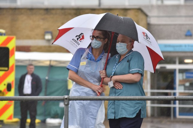 SOUTHEND ON SEA, ENGLAND - APRIL 28: Two nurses stand under an umbrella during the pouring rain outside Southend Hospital during the minute's silence for key workers who have died during the Coronavirus on April 28, 2020 in Southend on Sea, United Kingdom. The moment of silence, commemorating the key workers who have died during the Covid-19 pandemic, was timed to coincide with International Workers' Memorial Day. At least 90 NHS workers are reported to have died in the last month, in addition to transport employees and other key workers. (Photo by John Keeble/Getty Images)