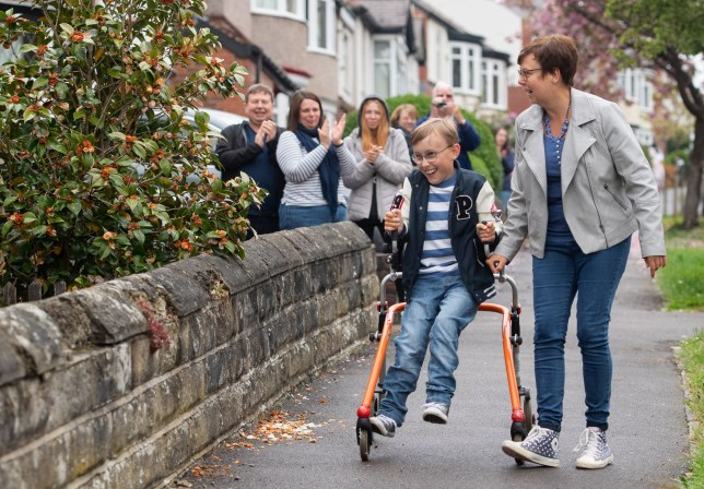Tobias Weller, who has cerebral palsy and autism, is cheered on by neighbours as he walks along the street